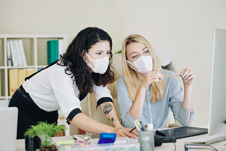 Two women work together with masks on
